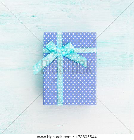 Blue gift box with ribbon on pastel background. Copy space top view father's day Christmas special occasion present. Square