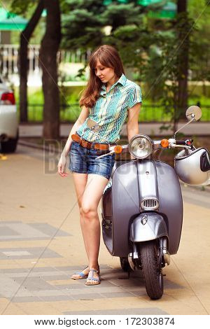 Young Beautiful Woman Poses Near The Scooter In City Park. Summertime