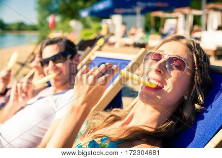 Woman and man eating ice cream on beach