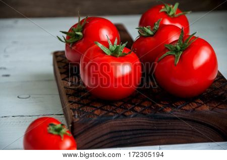 A Group Of Fresh Tomatoes Over A Wooden Board On A Whte Background