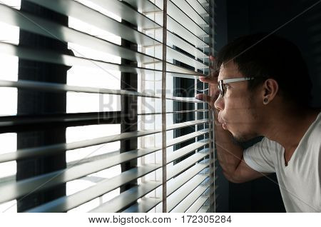 Asian man is looking through a wooden blind is on a window.