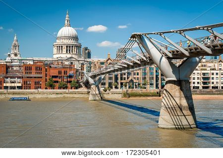 London United Kingdom - July 19 2013: View of Millennium footbridge across river Thames and St. Paul's cathedral on background. Unidentified people present on picture.