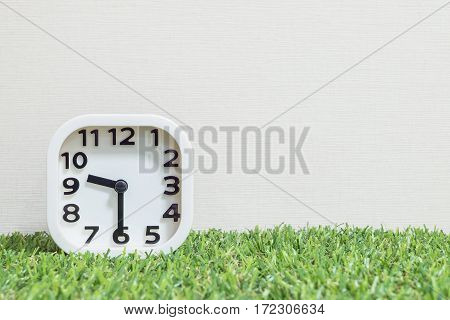 Closeup white clock for decorate show a half past nine or 9:30 a.m. on green artificial grass floor and cream wallpaper textured background with copy space