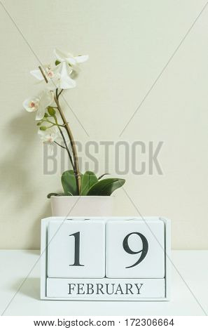 Closeup white wooden calendar with black 19 february word with white orchid flower on white wood desk and cream color wallpaper in room textured background in selective focus at the calendar