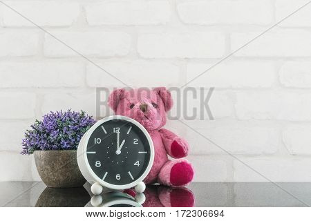 Closeup black and white alarm clock for decorate in 1 o'clock with bear doll and plant on black glass table and white brick wall textured background with copy space