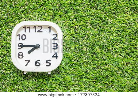 Closeup white clock for decorate show a quarter to eight or 7:45 a.m. on green artificial grass floor textured background with copy space