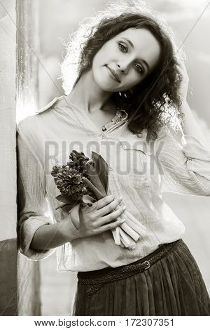 Happy young woman with flowers on city street. Stylish fashion model outdoor