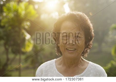 Portrait of healthy Asian senior woman smiling at outdoor nature park, morning beautiful sunlight background.