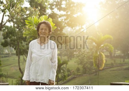 Portrait of healthy Asian senior woman standing at outdoor nature park, morning beautiful sunlight background.