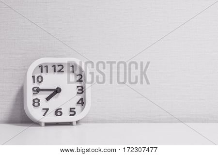 Closeup white clock for decorate show a quarter to eight p.m. or 7:45 a.m. on white wood desk and cream wallpaper textured background in black and white tone with copy space