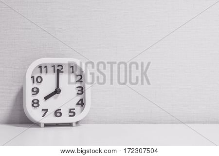 Closeup white clock for decorate in 8 o'clock on white wood desk and cream wallpaper textured background in black and white tone with copy space