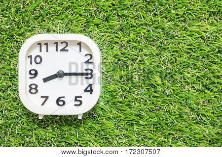 Closeup white clock for decorate show a quarter past eight or 8:15 a.m. on green artificial grass floor textured background with copy space