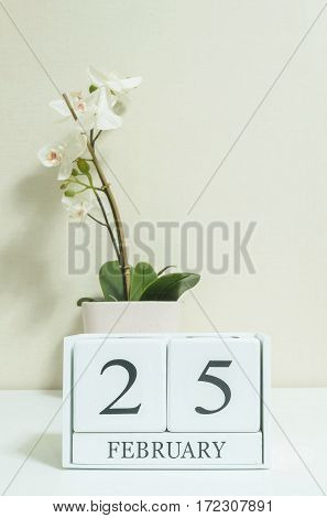 Closeup white wooden calendar with black 25 february word with white orchid flower on white wood desk and cream color wallpaper in room textured background in selective focus at the calendar