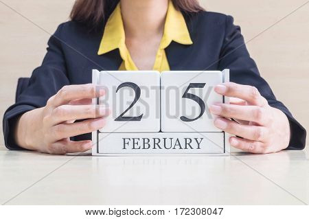 Closeup white wooden calendar with black 25 february word in blurred working woman hand on wood desk in office room in selective focus at the calendar