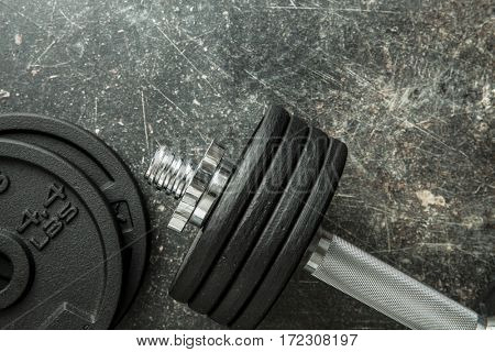 The metal dumbbell on old table.
