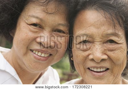 Portrait of healthy happy Asian seniors mother and daughter laughing at outdoor nature park, morning beautiful sunlight background.