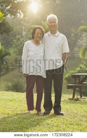 Portrait of healthy and happy Asian seniors retiree couple walking at outdoor nature park, morning beautiful sunlight background.