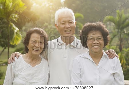 Group of healthy happy Asian seniors celebrating friendship at outdoor nature park, in morning beautiful sunlight at background.