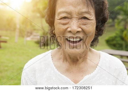 Portrait of healthy happy Asian senior woman laughing at outdoor nature park, morning beautiful sunlight background.