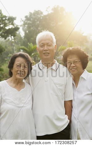 Group of healthy happy Asian seniors enjoy retired life at outdoor nature park, in morning beautiful sunlight at background.