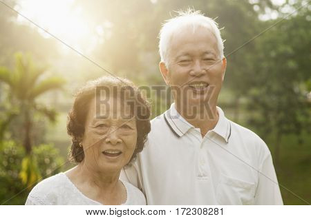 Portrait of healthy and happy Asian seniors retiree couple enjoying life at outdoor nature park, morning beautiful sunlight background.