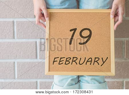 Closeup calendar at the cork board in hand of asian woman in front of her legs with 19 february word on brick wall textured background