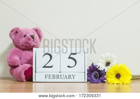 Closeup surface white wooden calendar with black 25 february word on brown wood desk and cream color wallpaper in room textured background with copy space in selective focus at the calendar