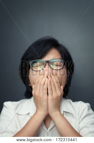 Close up of sleepy young asian woman yawning with isolated on grey wall background. Tired and sleepy of glasses girl woman from overwork. Sleepy of business woman. Sad woman isolated on grey wall. Short hair female sneezing. ILLness depression and allergy