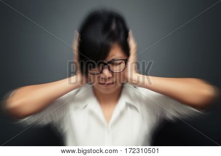 Blurred and de-focused of stress concept. Worried stressed face of asian woman expression. Stressed woman wear glasses headache with migraine headache pain. Business woman holding head with hands.
