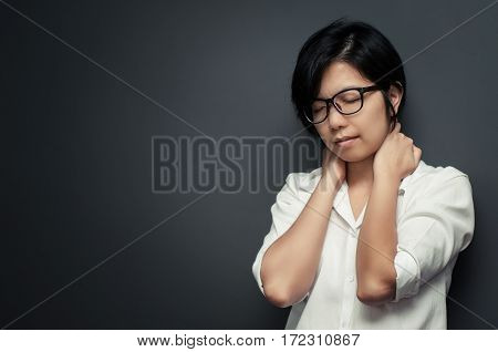 Asian young woman pain in neck. Glasses woman be ill and neck pain. Copy space.