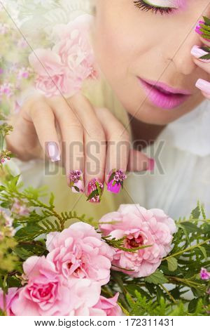 Multicolored pastel manicure with a design of natural flowers on female hand close up.Summer nail design.