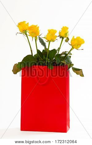 Yellow roses bouquet in a red paper bag, isolated on white background.
