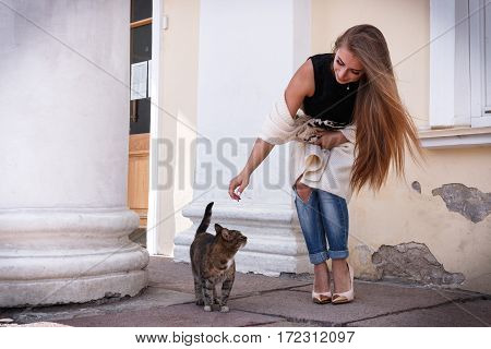 Fashion Of Nice Pretty Young Hipster Woman Playing With A Cat, He Leaned Down, Hair Flying.