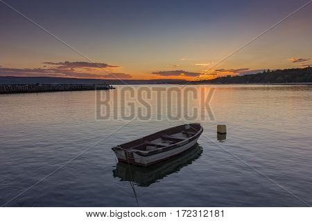 Beautiful light composition and mood of the boat in calm water at sunset