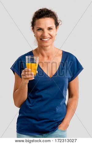 Middle aged woman holding a glass with orange juice
