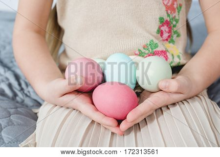 Close-up partial view of little girl holding colorful Easter eggs in hands