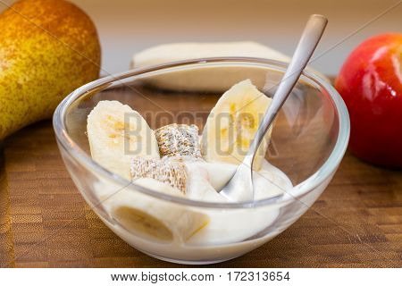Breakfast yogurt in glass bowl with fruit and cereals