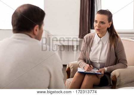 Typical workdays. Pleasant nice young woman speaking with the patient and making notes while having a psychological session with him