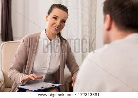 Stay optimistic. Cheerful beautiful female psychologist smiling and giving psychological advice to her patient while working with him