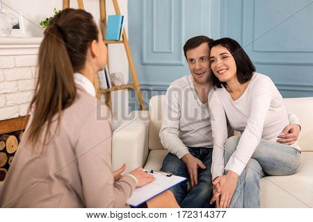 Finding a solution. Cheerful positive pleasant couple looking at their psychologist and smiling while finding a solution to their problem