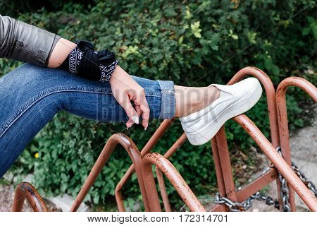 Teenager Girl Is Sitting On Metal Rods, Bicycle Parking, Rock 'n' Roll. Rock Style. Female Leg And H