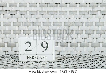 Closeup surface white wooden calendar with black 29 february word on blurred weave wood chair textured background with copy space in selective focus at the calendar
