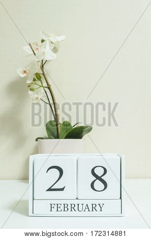 Closeup white wooden calendar with black 28 february word with white orchid flower on white wood desk and cream color wallpaper in room textured background in selective focus at the calendar
