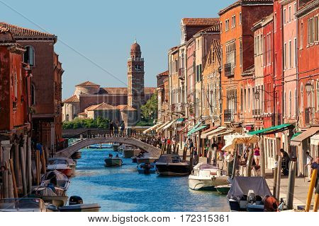 MURANO, ITALY - AUGUST 26, 2016: Boats on narrow canal along colorful houses of Murano - small island in Venetian lagoon, popular tourist destination, famous for its glass making.