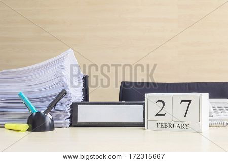 Closeup white wooden calendar with black 27 february word on blurred brown wood desk and wood wall textured background in office room view with copy space in selective focus at the calendar