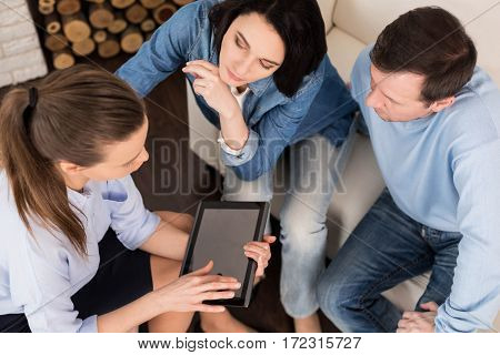 Psychological session. Pleasant confident female therapist using a tablet and showing something on its screen to the couple while having a psychological session with them