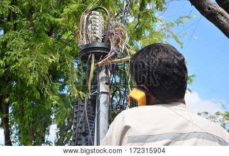 technician is plugging in a network cable to the line socket.