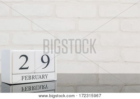 Closeup white wooden calendar with black 29 february word on black glass table and white brick wall textured background with copy space in selective focus at the calendar