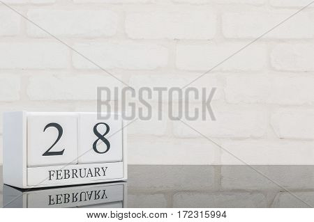 Closeup white wooden calendar with black 28 february word on black glass table and white brick wall textured background with copy space in selective focus at the calendar