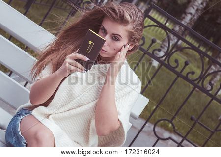 Girl Sitting On Bench And Looking At The Phone As In A Mirror, She Adjusts Makeup.